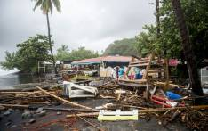 People stand next to debris at a restaurant in Le Carbet, on the French Caribbean island of Martinique, after it was hit by Hurricane Maria, on September 19, 2017. Picture: AFP