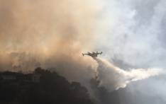 A fire fighting Canadair aircraft drops water over a fire near Carros, southeastern France, on July 24, 2017. Valery HACHE / AFP