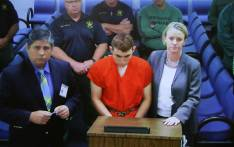 Hector Romero Asst. Public Defender (L) and Melisa McNeill, Public Defender (R) are seen on screen at the first appearance court for high school shooting suspect Nikolas Cruz (C) on 15 February 2018 at Broward County Court House in Fort Lauderdale, Florida. Picture: AFP