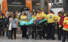 A man lies on a stretcher as emergency personnel gather on a platform in Barcelona's Francia terminus on 28 July 2017. Picture: AFP.