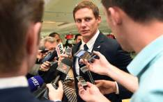 Stephen Larkham (C) speaks to the media at Sydney Airport on 28 October 2016 as the Wallabies depart for their European tour. Picture: AFP.