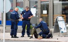 Police officers stand next to a person lying on the pavement in the Finnish city of Turku where several people were stabbed on August 18, 2017. Picture:  AFP.