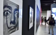 "A man walks near a portrait (1953-1954) of late Spanish artist Salvador Dali displayed on a wall during the exhibition ""Sorprendeme!"" (Surprise me, in Madrid on 30 November 2016. Picture: AFP"
