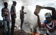 FILE: Opposition supporters hold up bricks as they block streets and burn tyres during a protest in Kisumu, Kenya, on 11 October 2017. Picture: AFP.