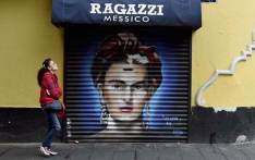 A woman walks past a mural of Mexican artist Frida Kahlo at Mesones Street, as part of a municipal government programme aimed at restoring public spaces in Mexico City's historic centre, on 30 August 2017 in Mexico City. Picture: AFP