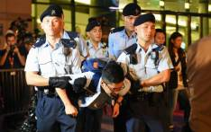 Hong Kong's youngest lawmaker and former Umbrella Movement leader Nathan Law is detained by police after he and other demonstrators staged a sit-in protest at the Golden Bauhinia statue, given to Hong Kong by China to mark the 1997 handover, in front of the Convention and Exhibition Centre in Hong Kong on June 28, 2017. Picture: AFP.