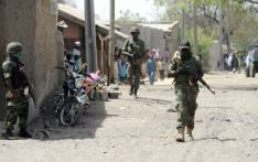 A file photo taken on 30 April, 2013 shows soldiers walking in the street in the remote northeast town of Baga, Borno State. Boko Haram launched renewed attacks around a captured town in restive northeast Nigeria this week, razing at least 16 towns and villages, a local government and a union official told AFP on 8 January, 2015. Picture: AFP.