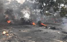 Burning tyres are seen on the road metres away from where Ocean View residents are gathered during a protest against gangsters in the area. Picture: Kevin Brandt/EWN.