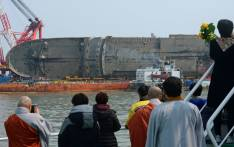 People and relatives of victims of the Sewol ferry watch the ongoing salvage operation off the coast of South Korea's southern island of Jindo on March 28, 2017. Picture: AFP