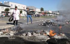 Residents of the Steen Villa complex throw tires on to a fire in the middle of Military Road in Retreat. The residents protested when the Social Housing Company wanted to evict members of the community who refuse to pay rent. Picture: Bertram Malgas.