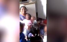 A screengrab of a woman allegedly abusing a baby.