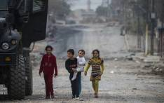 FILE: Children emerge from their houses to greet soldier from the Iraqi Special Forces 2nd division during a lull in the fighting with IS fighters while pushing into the Aden neighbourhood in Mosul in November 2016. Picture: AFP.