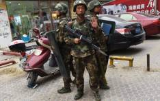 FILE: Paramilitary police officers standing guard outside a shopping mall in Hotan, in China's western Xinjiang region. Picture: AFP