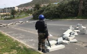 A police officer stands guard on the road in Hangberg during a protest by residents who are reportedly angry at the Agriculture, Forestry and Fisheries Department's decision to cut fishing quotas. Picture: Shamiela Fisher/EWN