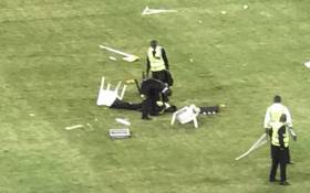 A female security guard lays motionless on the ground after being attacked by angry soccer fans after Kaizer Chiefs fans invaded the pitch during the Nedbank Cup match against Free State Stars at Moses Mabhida on 21 April 2018. Picture: Screengrab