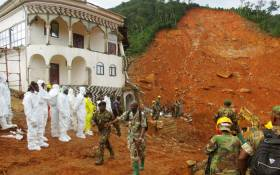 FILE: Search and rescue team members and soldiers operate near a mudslide site and damaged building near Freetown, Sierra Leone on August 15, 2017. Picture: AFP