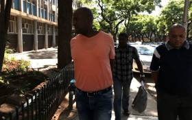 Crime Intelligence operative Morris Tshabalala (in orange) arrives at the Pretoria Commercial Crimes Court on 19 January 2018. Picture: Barry Bateman/EWN.