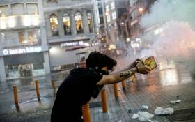 A protester fires fireworks at Turkish riot police during a demonstration on July 20, 2015 in Istiklal avenue in Istanbul, after a suicide bombing in the Turkish town of Suruc near the border with Syria killed at least 31. A suspected Islamic State suicide bomber killed at least 31 people on July 20 in an attack on a Turkish cultural centre where activists had gathered to prepare for an aid mission in the nearby Syrian town of Kobane. AFP