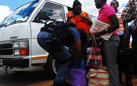 Police officers search commuters at a road block in Pretoria during a crime combating operation. Picture: EWN.