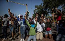 University of Johannesburg students raise their hands in front of a riot police line while blocking a motorway during clashes on September 28, 2016 outside the University of Johannesburg Campus. Picture: AFP