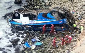 Handout picture released by Peruvian agency Andina showing rescuers, police and firefighters working at the scene after a bus plunged around 100 meters over a cliff after colliding with a truck on a coastal highway near Pasamayo, around 45 km north of Lima, and killing at least 25 people on 2 January, 2018. Picture: AFP.