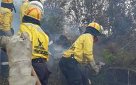 A team from Working on Fire mopping up an area affected by a fire near Camps Bay. Picture: @wo_fire/Twitter.