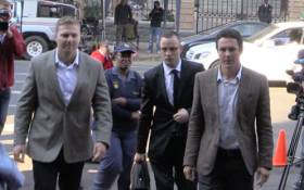 Oscar Pistorius is escorted into the High Court in Pretoria ahead of his murder trial on 5 May 2014. Picture: Christa Eybers/EWN.