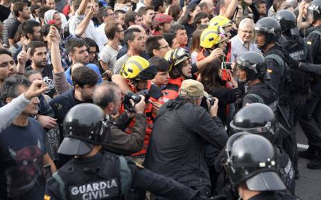 Firemen hold the people in front of Spanish Guardia Civil officers outside a polling station in San Julia de Ramis, on 1 October 2017, on the day of a referendum on independence for Catalonia banned by Madrid. Picture: AFP.