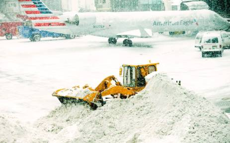FILE: A front loader plows snow at LaGuardia Airport in the Queens borough of New York City. Picture: AFP