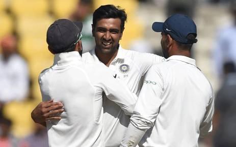 FILE: Indian cricketer Ravichandran Ashwin (C) celebrates with captain Virat Kohli (L) after India won the second Test cricket match against Sri Lanka at the Vidarbha Cricket Association Stadium in Nagpur on 27 November 2017. Picture: AFP