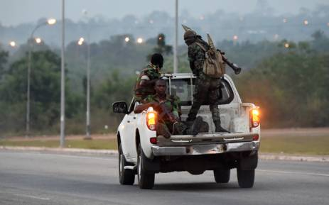 Ivorian soldiers, part of a group of soldiers sent from Bouake as reinforcements, drive down a road in Yamoussoukro on 17 January, 2017. Picture: AFP.