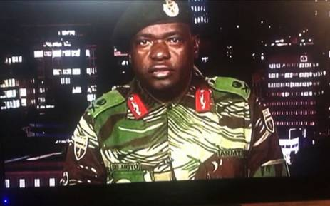 This screengrab taken early on 15 November 2017 from a television broadcast on the Zimbabwe Broadcasting Corporation (ZBC) shows Zimbabwe Major General Sibusiso Moyo reading a statement at the ZBC broadcast studio in Harare. Picture: AFP.