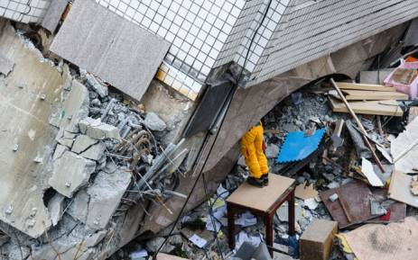 A rescue worker clears debris to make way for the recovery of the dead bodies of a Hong Kong Canadian couple from the Yun Tsui building, in the Taiwanese city of Hualien on 9 February 2018, following a 6.4-magnitude quake. Picture: AFP