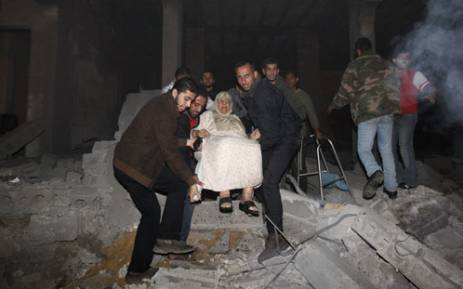 Palestinian men evacuate an elderly woman following an Israeli air strike on November 14, 2012 in Gaza City. Picture: AFP