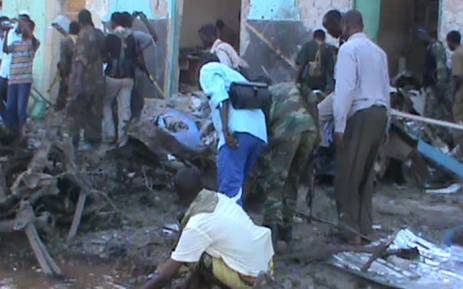People and soldiers search in the rubble of a destroyed building on 28 February, 2016 in Baidoa after twin explosions in the Somali city killed at least 30 people. Picture: AFP.