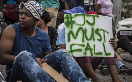 A University of the Free State student holds up a placard calling for the removal of the institutions vice chancellor Prof. Jonathan Jansen during protests on main campus in Bloemfontein. Picture: Reinart Toerien/EWN.