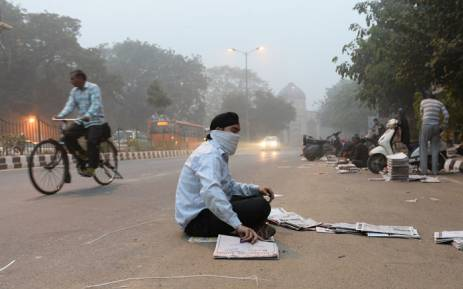 FILE: An Indian newspaper vendor wears a mask whilst he sorts newspapers on a road as heavy smog covers New Delhi on 7 November 2016. Picture: AFP.