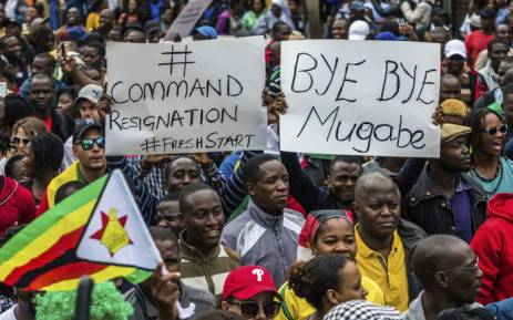 FILE: People carry placards during a demonstration demanding the resignation of Zimbabwe's President Robert Mugabe on November 18, 2017 in Harare. Picture: AFP