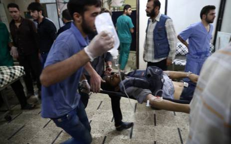 FILE: An injured Syrian man arrives on a stretcher to receive treatment at a makeshift hospital, on the eastern outskirts of Damascus, Syria. Picture: AFP.