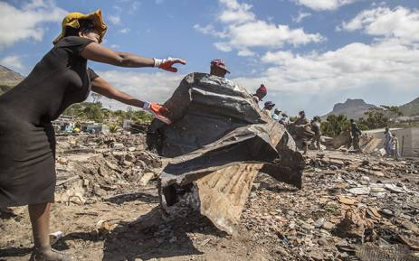 "FILE: ""Residents of the Imizamo Yethu informal settlement in Hout Bay, Cape Town, help to clear the rubble on 28 December 2015 after a fire ripped through a section. Picture: Aletta Harrison/EWN"