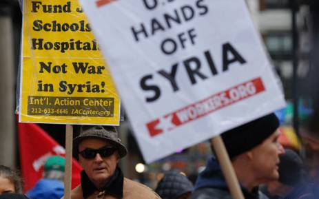 A man holds a placard during an anti-war protest after President Donald Trump launched airstrikes in Syria, 15 April 2018 in New York City. Picture: AFP