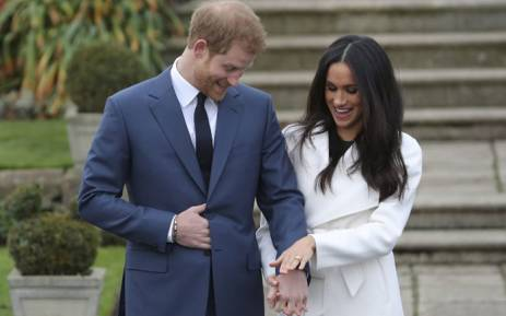 Britain's Prince Harry stands with his fiancée US actress Meghan Markle as she shows off her engagement ring while they pose for a photograph in the Sunken Garden at Kensington Palace in west London on 27 November 2017 following the announcement of their engagement. Picture: AFP.