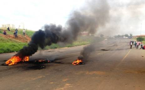 Residents blockade roads in Sebokeng with burning tyres and rubble during a violent service delivery protest, 6 February 2014. Picture: Sebabatso Mosamo/EWN.