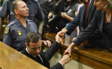 Oscar Pistorius holds the hands of family members as he is taken down to the holding cells after being sentenced to five years imprisonment for the culpable homicide killing of his girlfriend Reeva Steenkamp at the high court in Pretoria on 21 October 2014. Picture: Pool.