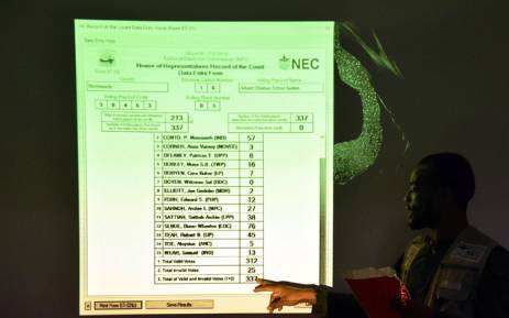 A member of Liberia's National Electoral Commission (NEC) points to results at a tally center in the capital Monrovia following the country's presidential and legislatives elections on 12 October 2017. Picture: AFP.