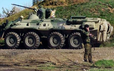 FILE: A Russian troop stands guard in front of an APC at a check-point in Crimea, near the town of Armyansk in 2014. Picture: AFP.