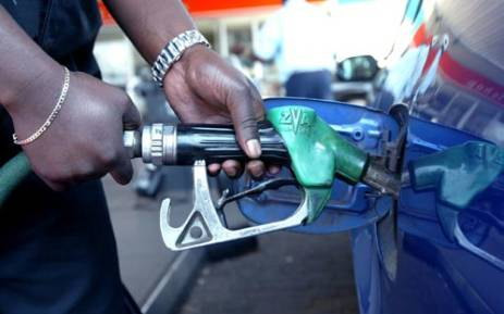 A petrol station attendant fills up a car tank. AFP