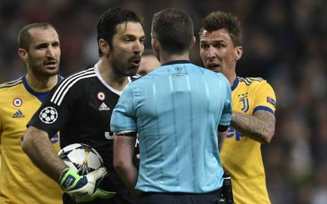 Juventus captain and goalkeeper Gianluigi Buffon (in black) confronts referee Michael Oliver after he awarded a penalty to Real Madrid in their UEFA Champions League match on 11 April 2018. Picture: AFP