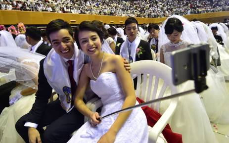 A couple takes a selfie during a mass wedding held by the Unification Church at Cheongshim Peace World Center in Gapyeong, east of Seoul, on 20 February 20 2016. Picture: Jung Yeon-Je Jung Yeon-Je / AFP.