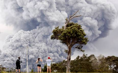People watch as ash erupts from the Halemaumau crater during ongoing eruptions of the Kilauea Volcano in Hawaii on 15 May 2018. Picture: Reuters